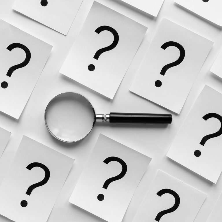 Diagonally orientated question marks and magnifier